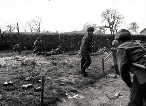 Infantry of the South Saskatchewan Regiment lying down and firing through a hedge near Dutch farmhouse, Oranje Canal, the Netherlands, April 12th, 1945.