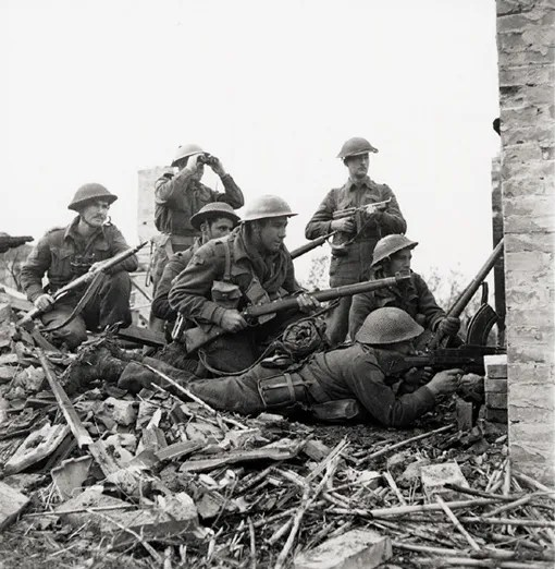 Platoon Commander Lieutenant I. Macdonald (with binoculars) ready to give order to attack at S. Leonardo di Ortona, Italy, 10 December 1943. Left to right, Sergeant J.T. Cooney, Privates A.R. Downie, O.E. Bernier, G.R. Young (kneeling, with Lee-Enfield rifle), Corporal T. Fereday and Private S.L. Hart (lying down with Bren gun) all of the 48th Highlanders.