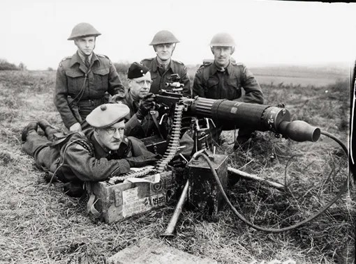 Officers of the Cameron Highlanders of Ottawa demonstrate the Vickers machine gun. Front, left to right: Major G.F. Clingdon, Lieutenant-Colonel H.V.D. Laing. Rear, left to right: Captain Roger Rowley, Lieutenants W.H. Armstrong and G.O. Handley. Lindfield, England, 8 April 1942.