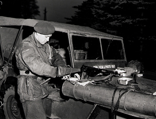 Sergeant C.M.G. Lattion, Canadian Army Film and Photo Unit, cleaning Sten gun, Lembeck, Germany 29 March 1945.