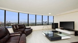 Glass-Top-Table-In-A-Modern-Apartment-Living-Room-Design-With-Brown-Leather-Sofa-And-Television