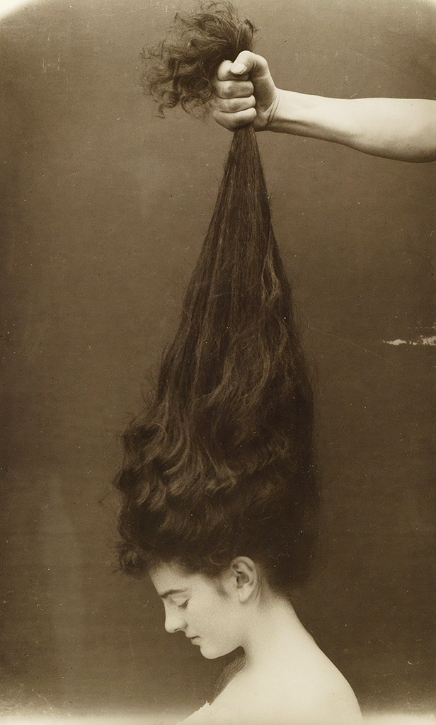 Hand grasping a beautiful young woman's long, dark hair. 'Bromide print, Circa 1910