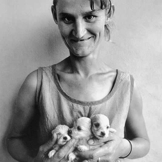 Roger Ballen Wife-of-abattoir-worker-holding-three-puppies-Orange-Free-State-1994
