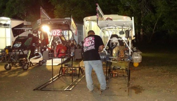Fred Buck wrenching on 2 karts