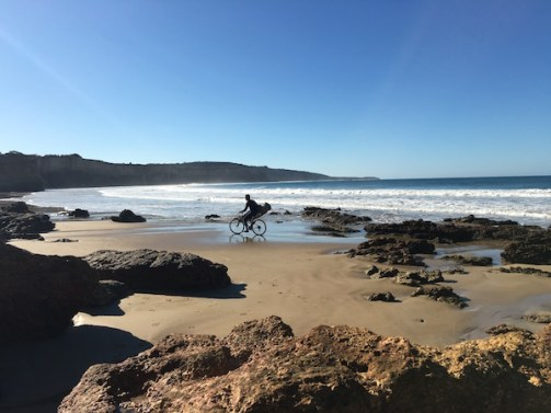 Man with surfboard riding a bike on Anglesea Beach, Great Ocean Road