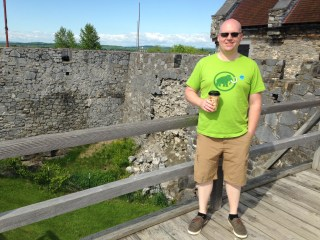 Kevin on a bridge with a crumbling wall behind.