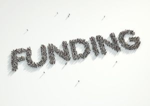 Aerial shot of a crowd of people forming the word Funding Concept for crowd funding platforms or projects that are supported financially by crowd funded websites.
