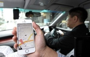 An Uber Japan Co. employee holds an Apple Inc. iPhone 5s showing a map on the Uber application for a photograph during a demonstration in Tokyo, Japan, on Wednesday, March 5, 2014. Uber Technologies Inc., the booking-app developer backed by Google Inc.s investment arm and Amazon.com Inc. founder Jeff Bezos, expanded to Tokyo using licensed taxi operators rather than private drivers. Photographer: Junko Kimura-Matsumoto/Bloomberg via Getty Images