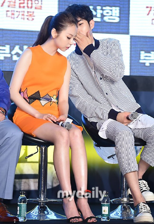 Image: Choi Woo Sik whispering to Sohee on stage during the press conference for the film Train to Busan