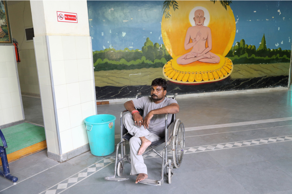 A man stricken by Polio waits to be taken into the rehabilitation centre for physiotherapy.