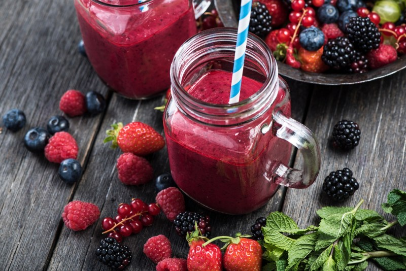 Summer berries smoothie in mason jar on rustic wooden table