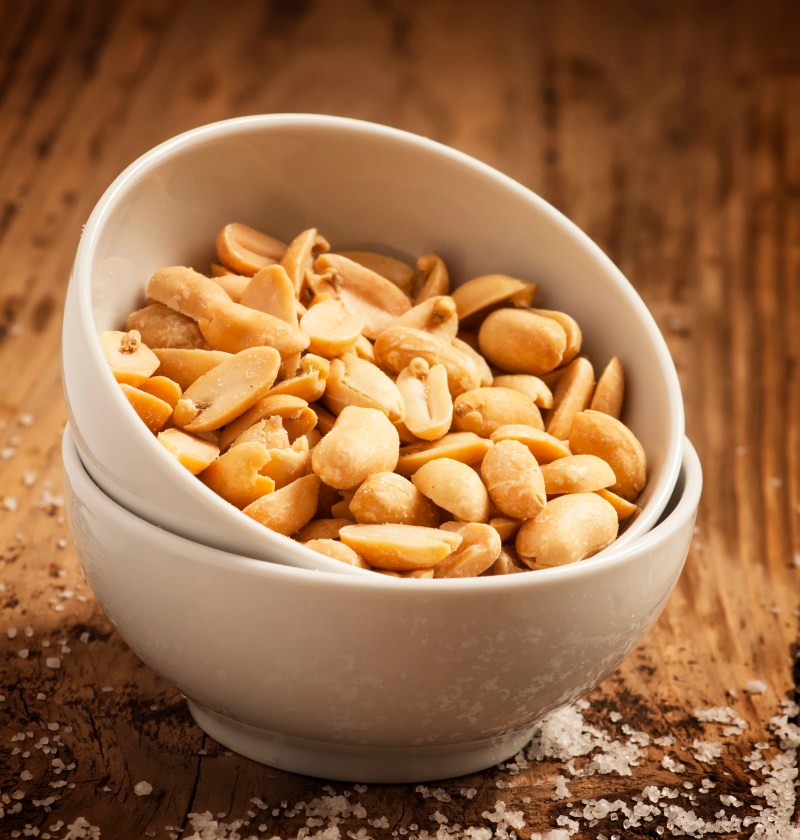Roasted peanuts and salt in a bowl on a wooden background, selective focus