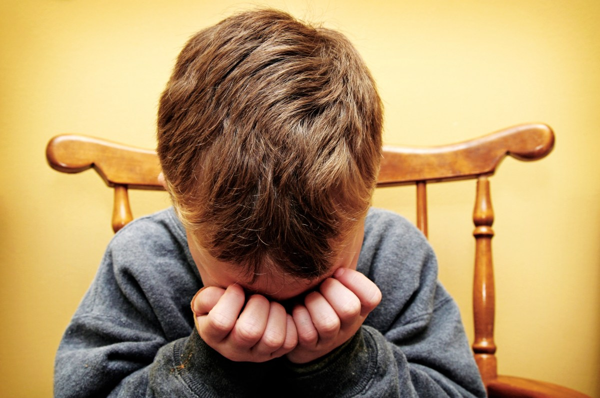 Young boy crying into his hands. Horizontal with copy space.