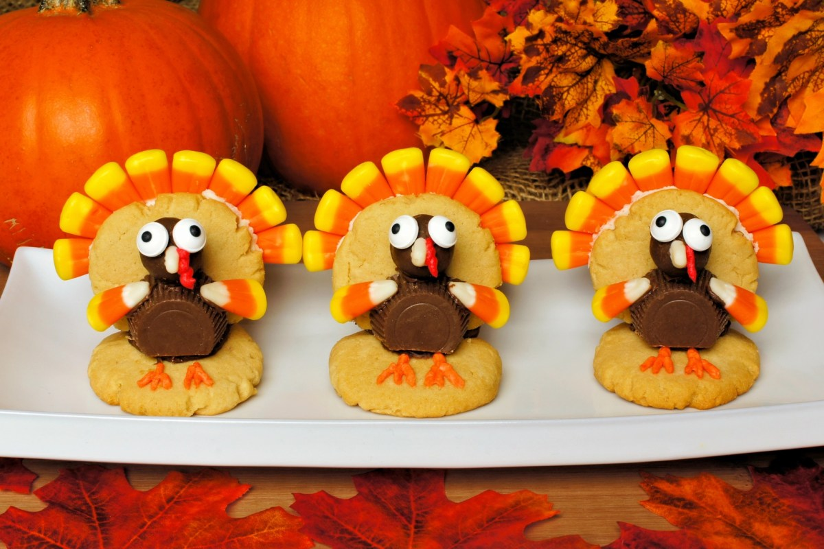Three Thanksgiving turkey shaped cookies on a plate with autumn leaves and pumpkins