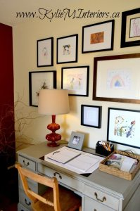 kids artwork gallery in kitchen with desk