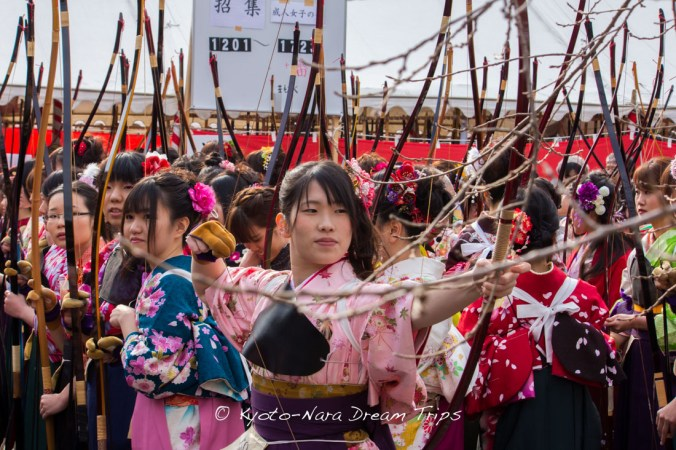 A sea of bows and a lady dressed in kimono practising before the final shoot-out at the archery (Toshiya-通し矢) contest in Sanjūsangen-dō (三十三間堂) in Kyoto today.