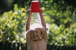 Niños refrescándose con un balde de agua