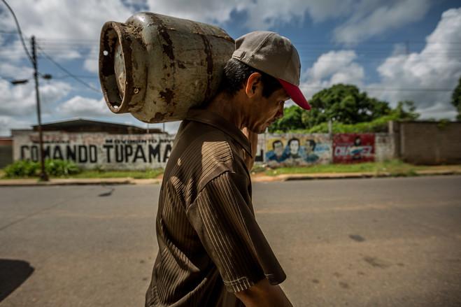 Cerca de los pozos donde se quema el petróleo, la gente hace fila por gas licuado. PHOTO: MIGUEL GUTIÉRREZ PARA THE WALL STREET JOURNAL