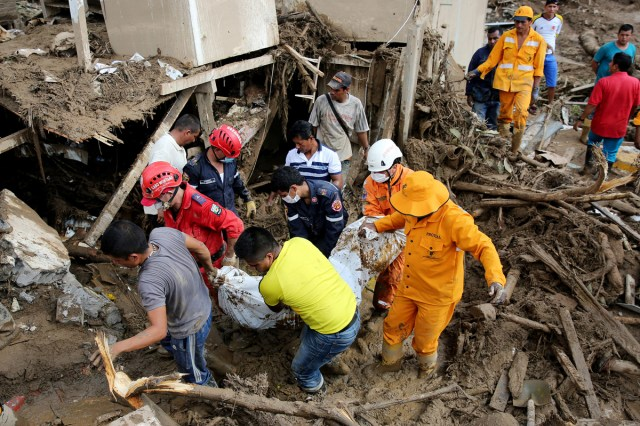 -FOTODELDIA- BOG201. MOCOA (COLOMBIA). 02/04/2017. Miembros de los equipos de emergencia rescatan el cuerpo de una mujer hoy, domingo 2 de abril de 2017, luego de una avalancha que afectó 17 barrios de la ciudad y que dejó más de 200 muertos en Mocoa, Putumayo (Colombia). El presidente de Colombia, Juan Manuel Santos, confirmó hoy que 210 personas fallecieron y 203 más resultaron heridas en la avalancha de tres ríos que arrasó parte de Mocoa, al tiempo que prometió la reconstrucción de esta ciudad ubicada en las selvas del sur del país. EFE/LEONARDO MUÑOZ