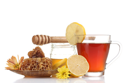 honey, lemon, honeycomb and a cup of tea isolated on white