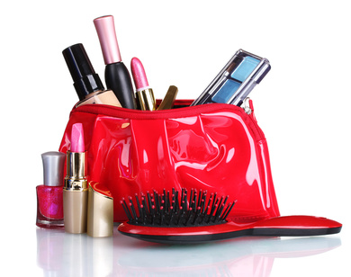 Beautiful red makeup bag and cosmetics isolated on white