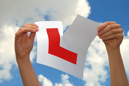 Woman holding ripped L plate after passing driving test