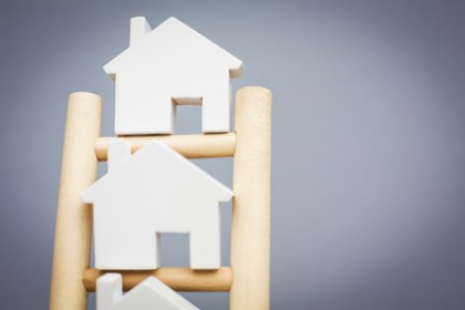 Model Houses On Rungs Of Wooden Property Ladder