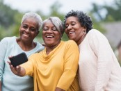 Friends taking a selfie.  A group of three senior, African American woman with a camera phone are posing for a photo.