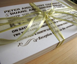 Stack of Fontography inspired laser cut wedding invitations with yellow ribbon