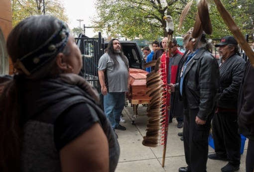 Casket bearers wait to carry the body of Dennis Banks. Banks, whose Ojibwe name was Nowacumig, lived near the town of Federal Dam on the Leech Lake Reservation in northern Minnesota. His family said that as Banks took his last breaths, son Minoh Banks sang him four songs for his journey. (Jerry Holt/Star Tribune via AP)