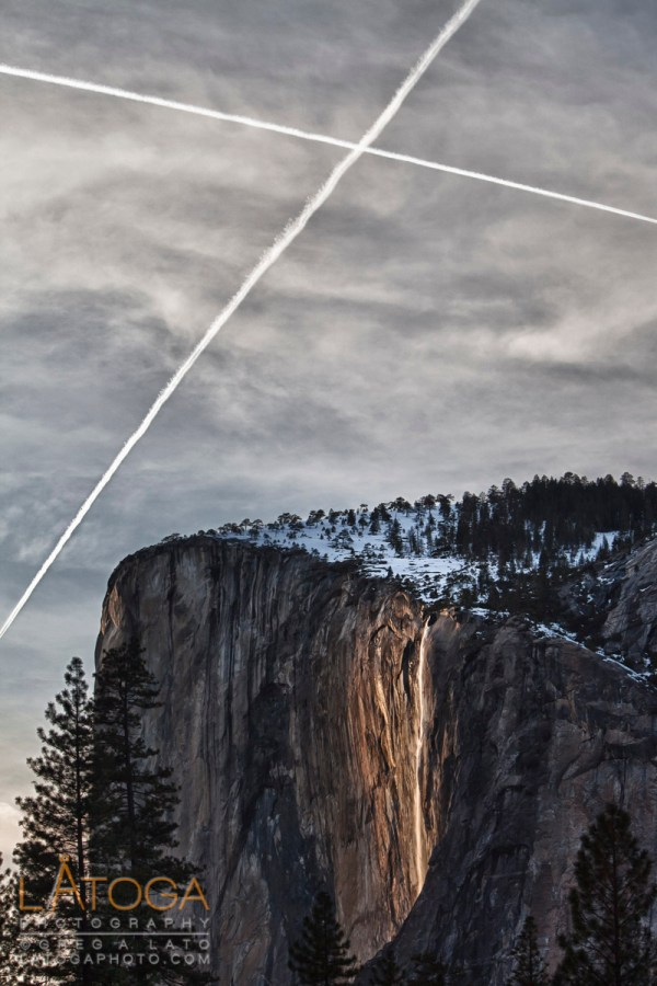 A pair of contrails marks the Horsetail Falls during it's bi-annual Firefall in Yosemite National Park, California. (HDR)
