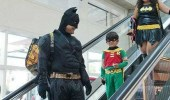 A meme of The Dark Knight Rises. Batman, Robin, and Batgirl riding down an escalator at Comic-Con. The Dark Knight Descends.