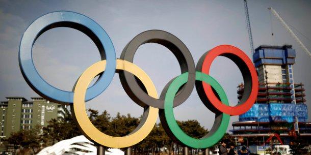 People walk past the Olympic rings in Gangneung, South Korea February 9, 2017. REUTERS/Kim Hong-Ji