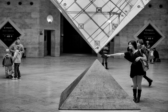 Paris, Louvre museum. Girl touching the pyramid.