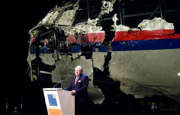 Mężczyzna stoi przy mównicy z mikrofonem na tle zrekonstytuowanego wraku samolotu w niebiesko czerwone linie