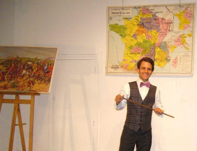 """Photo du spectacle de Maxime d'Abboville """"Histoire de France"""". Costume daté, baguette de maître d'école, carte de classe ancienne, tout est fait pour que le spectateur soit plongé dans une image d'Épinal fantasmant un âge d'or de l'enseignement de l'histoire en France."""
