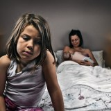 Unhappy girl with mother and new baby in background --- Image by © Justin Paget/Corbis