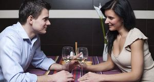 Attractive young couple drinking wine and flirting
