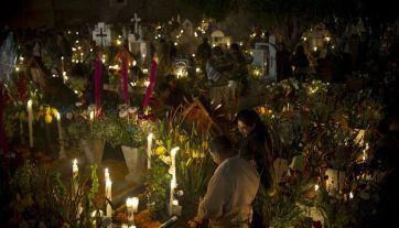 Residents of Mixquic town visit a local cemetery to place flowers, food, candles and balloons at the tombs of their beloved during the celebration of All Souls Day on November 2, 2015 in Mixquic, Mexico. AFP PHOTO / Yuri CORTEZ (Photo credit should read YURI CORTEZ/AFP/Getty Images)