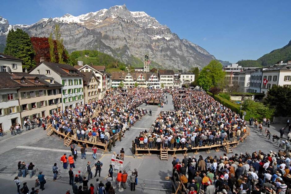Nei cantoni svizzeri dell'Appuntello Interno e di Glarona, ttutti i cittadini della comunità rurale si riuniscono in assemblea in una piazza e votano per alzata di mano per eleggere gli amministratori e deliberare leggi locali.