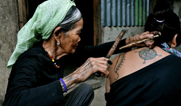 1_Donna Kalinga mentre esegue un tatuaggio