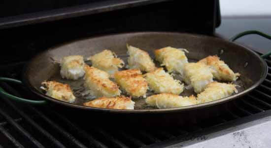 frying coconut crusted cod on the grill