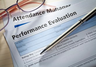 Performance Evaluation document with pen and glasses.