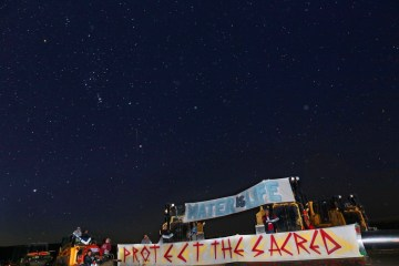 Protestors lock themselves to Dakota Access's machinery to halt construction. Photo by Matika Wilbur.