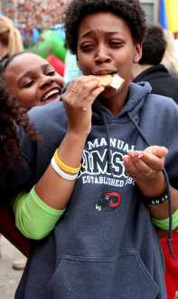 Jamila Bland (11) scarfs down gram cracker while being fe by Shelby Johnson (11) as they compete in the stick snack challenge at the carnival. Photo by Mesa Serikali