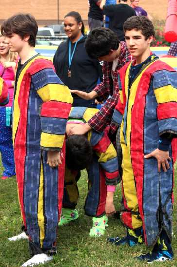 Students suit up in their velcro suits ready to be stuck to the velcro wall.