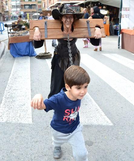 Caracterización de bruja en la horca arrastrada por un niño