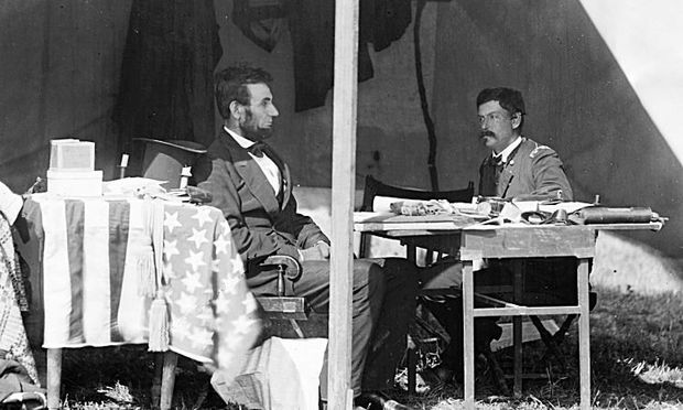 President Lincoln and General McClellan talk shop beside an American flag being used as a tablecloth.