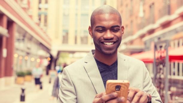 Smiling man using smart phone