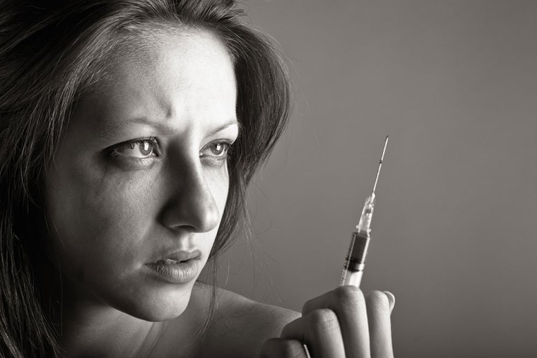 young woman contemplating syringe